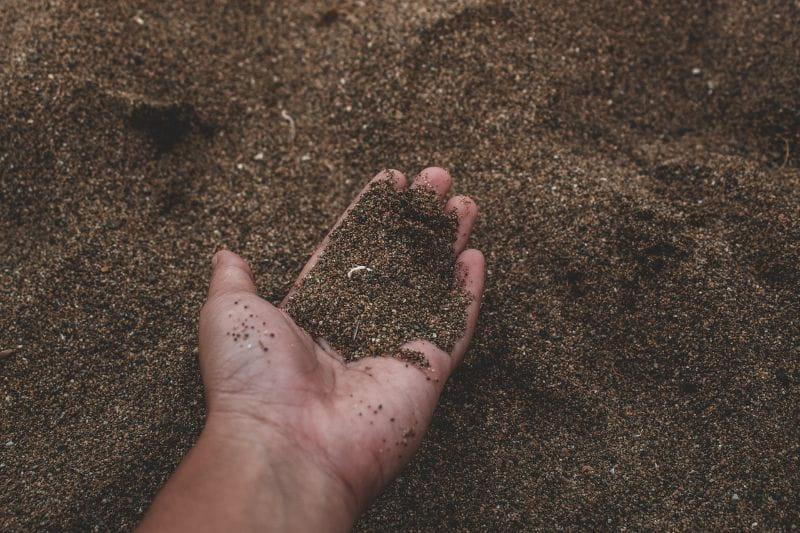 man holding soil in hand